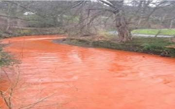 نهر يتحول لونه إلى البرتقالي بفعل الفيضانات في بريطانيا (بالصور)